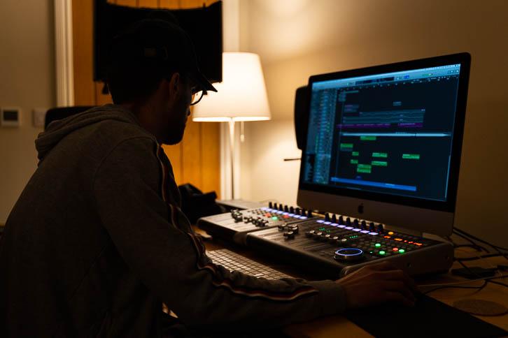 Alastair sitting behind music iMac in dark bedroom studio
