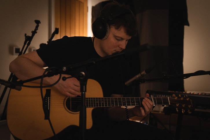 Kelvin playing recording acoustic guitar in dark bedroom music room