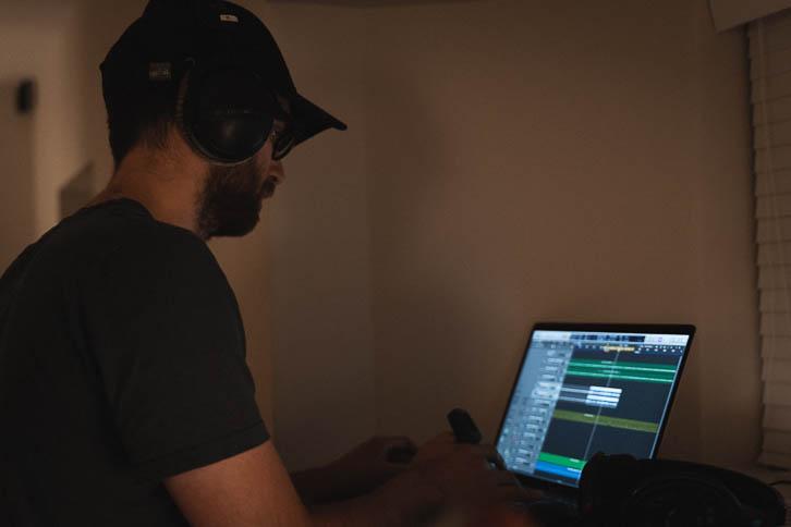 Alastair standing at windowsill working on music laptop in dark bedroom music room