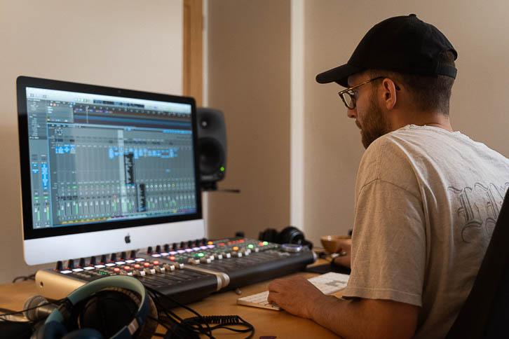 Alastair sitting behind music iMac in bedroom studio