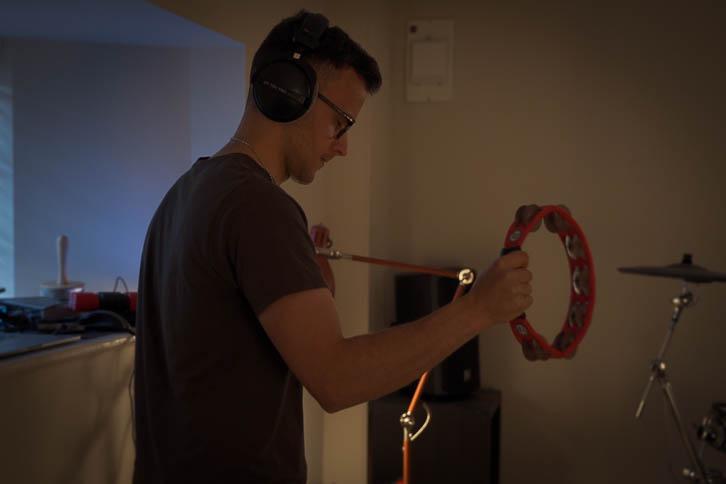 Gavin playing tambourine in a dark bedroom music room