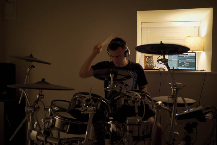Gavin recording drums in a dark bedroom music room